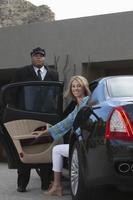 glückliche Frau, die vom Auto herunterkommt foto