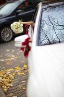 Braut winkt Hand vom Auto, das Blumenstrauß hält foto