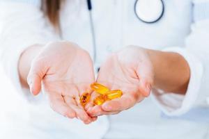 gelbe Pillen in den Händen foto