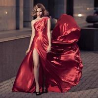 junge schöne Frau im flatternden roten Kleid. Stadthintergrund.