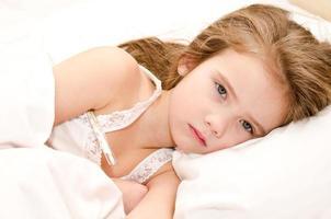 krankes kleines Mädchen im Bett liegen foto