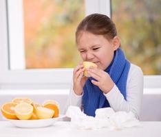 Mädchen versucht, eine Orangenscheibe zu probieren foto