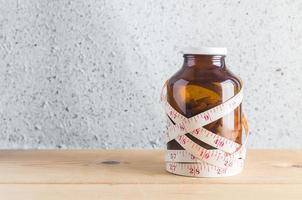 Medizin mit Maßband auf Holzhintergrund foto