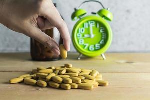 Hand wählen Sie eine Medizin auf Holzhintergrund foto