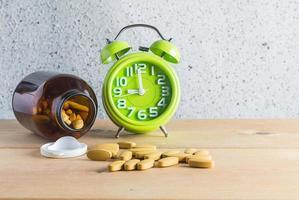 Medizin und Uhr auf Holzhintergrund foto