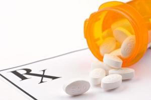 verschreibungspflichtige Tabletten, die aus einem orangefarbenen Behälter verschüttet werden foto