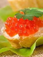 Sandwich mit rotem Kaviar, Butter und Gurke foto