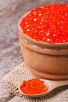 roter Lachskaviar in einem Holzlöffel und einem Fass foto