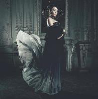 Eleganzfrau mit fliegendem Kleid im Palastraum foto