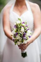 schöner Hochzeitsstrauß in den Händen der Braut foto