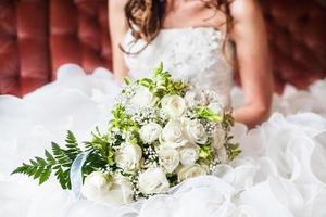 Braut hält hellen Hochzeitsstrauß foto