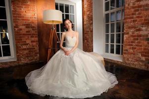 schöne Braut sitzt posierend in ihrem Hochzeitskleid. Studio.