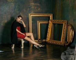Schönheit reiche brünette Frau im Luxusinnenraum nahe leeren Rahmen foto