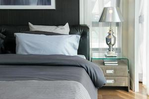 Luxuslampe und Bücher auf Nachttisch im Schlafzimmer