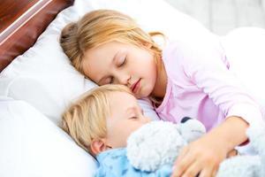 kleines Mädchen und Junge schlafen auf weißem Bett foto