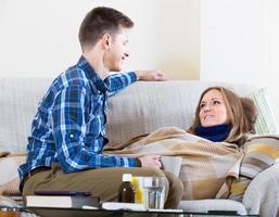 Frau mit Kälte auf der Couch liegend, Freund kümmert sich