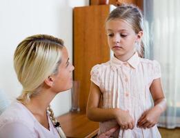 krankes Mädchen mit Magenschmerzen und besorgter Mutter drinnen foto