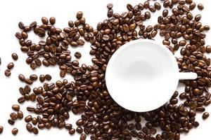 weiße Kaffeetasse und Kaffeebohnen.