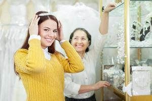 Verkäuferin hilft Braut bei der Auswahl des Brautkranzes foto