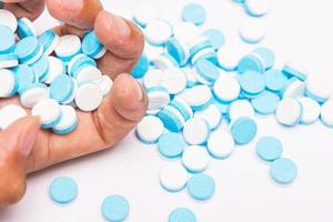 weiße und blaue Tablettenpillen zur Hand foto