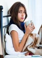 krankes junges Mädchen mit heißem Tee und Medikamenten drinnen foto