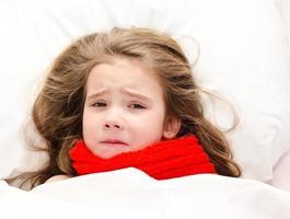 krankes kleines Mädchen, das im Bett im roten Schal liegt foto