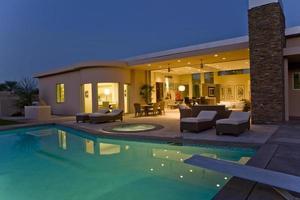 Haus mit Sonnenliegen auf der Terrasse am Pool in der Abenddämmerung foto