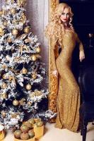 Frau im luxuriösen goldenen Kleid, das neben einem Weihnachtsbaum aufwirft foto