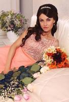 schöne Braut mit dunklem Haar posiert mit Blumenstrauß foto