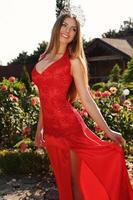 schönes Mädchen in elegantem rotem Kleid und luxuriöser Krone