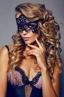 sinnliche Frau mit luxuriösem blondem Haar mit Maske im Gesicht foto