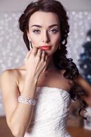 schöne elegante Braut mit dunklem Haar, das im Studio aufwirft foto