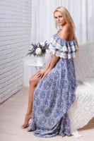 schönes Mädchen, das auf der Kante des Sofas sitzt foto
