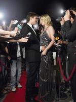 Paar umarmt auf rotem Teppich, umgeben von Paparazzi