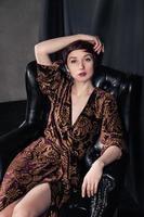 Nahaufnahme der Frau, die kurzes Kleid trägt, das im Sessel sitzt foto