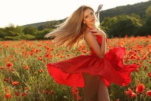 Mädchen im eleganten Kleid, das im Sommerfeld der Mohnblumen aufwirft
