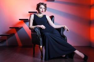 schöne elegante Frau, die auf einem Sessel sitzt foto
