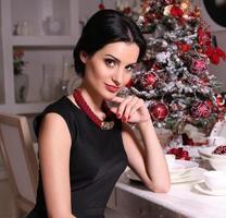 schöne Frau, die neben s geschmücktem Weihnachtsbaum aufwirft foto