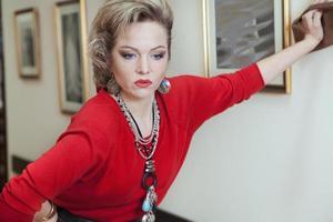 schöne blonde Frau in einem roten Pullover foto
