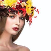 schönes Mädchen mit hellem Herbstkranz von Blättern und Blumen