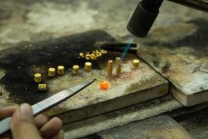 Goldschmied arbeitet mit einer unvollendeten Arbeit. foto