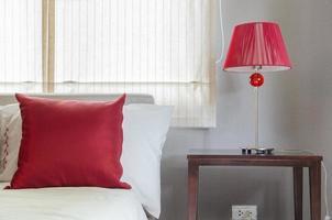 Schlafzimmer mit rotem Kissen und Lampe foto