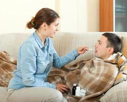 Mädchen, das dem kranken Ehemann Medikamente gibt foto