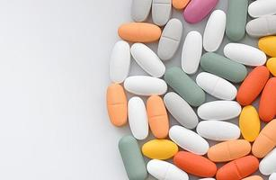 Stapel verschiedener Pillen in Blasen, die auf weißem Hintergrund isoliert sind foto
