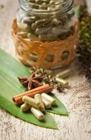 Kräuterkapsel mit grünem Kräuterblatt auf Holz foto