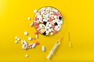 Spritze und bunte Pille und Kapseln auf Hintergrund foto