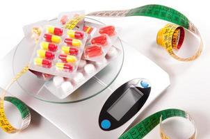 Maßband und Medikament über Küchenwaage foto
