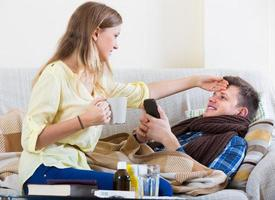 Frau kümmert sich um Ehemann mit Kamin foto