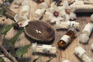 Flaschen mit Homöopathiekügelchen und Löffel foto