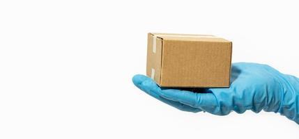 Lieferbote hält Pappkarton in Gummihandschuhen foto